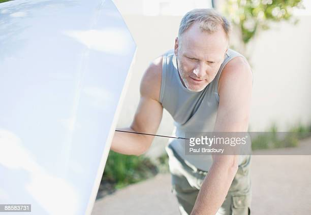 Man checking oil in car