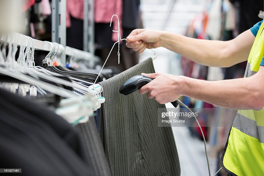 Man checking pair of trousers in warehouse : Stock Photo
