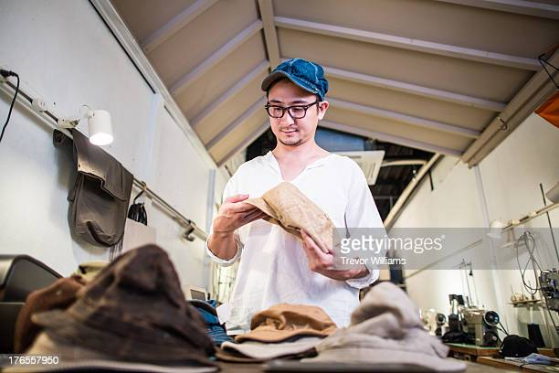 A man checking quality of a hat in his shop