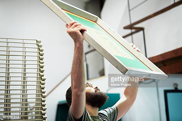 Man checking quality of silk screen