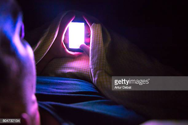 Man checking smartphone at late night inside bed with bright light from point of view. Nomophobia. Vibranxiety, ringxiety and fauxcellarm.