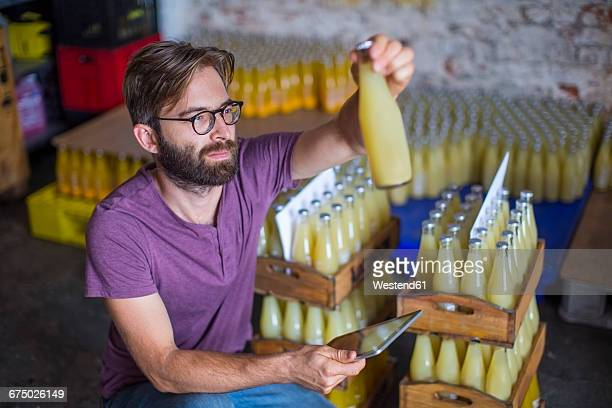 Man checking stock of juice bottles in warehouse