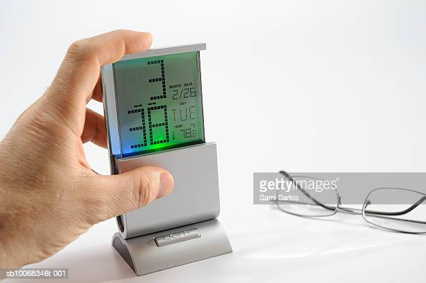 Man checking time on digital alarm clock, close-up of hand