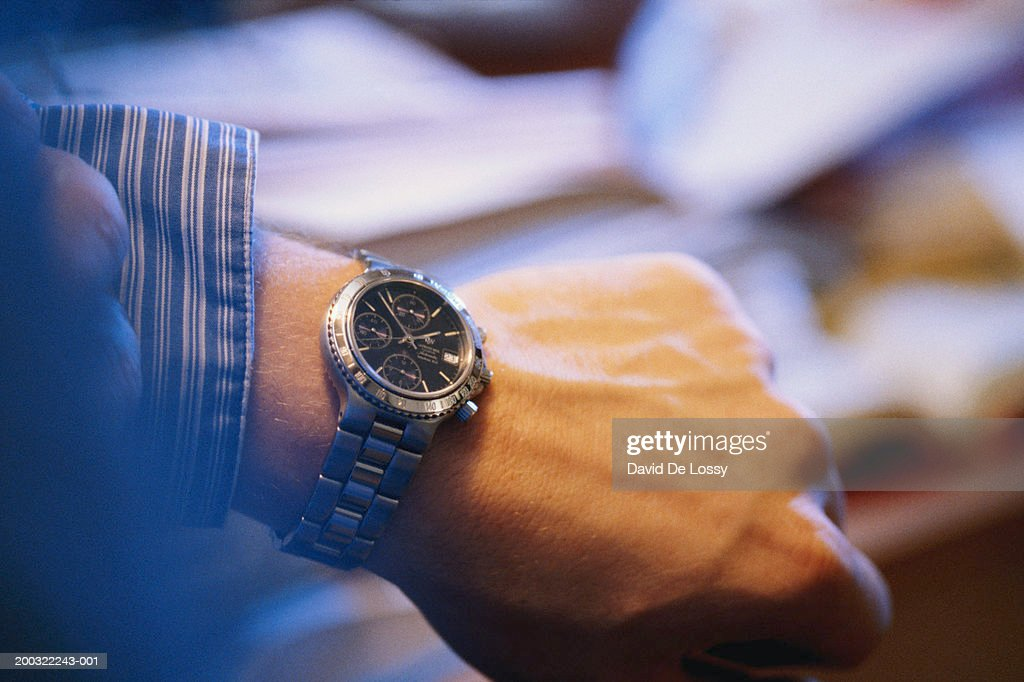Man checking time on wrist watch, close-up