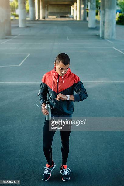 Man checking time while standing on street