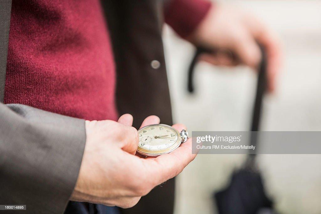 Man checking watch on city street : Stock Photo