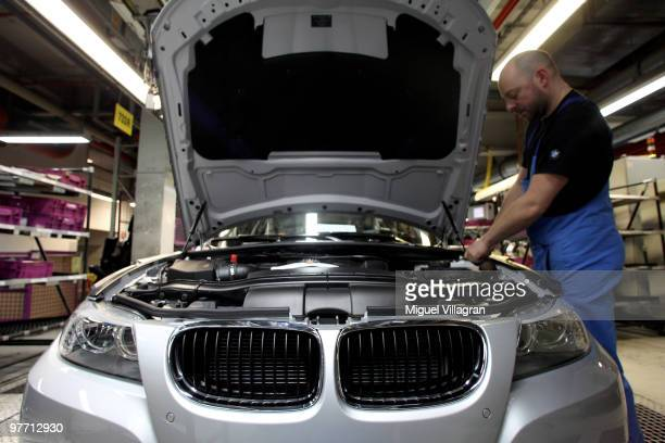 A man checks a car on the BMW 3series production line at the BMW factory on March 15 2010 in Munich Germany The German car maker will present the...