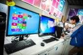 A man checks a computer next to a screen displaying Microsoft's new Windows 8 operating system in Hong Kong on October 26 2012 Microsoft took a big...