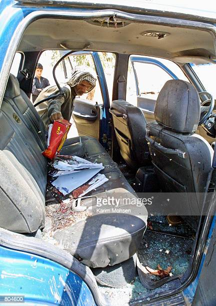 A man checks a damaged car that was allegedly hit by a missile during a raid April 29 2001 in the Najaf province 180 km south of Baghdad Iraq said...