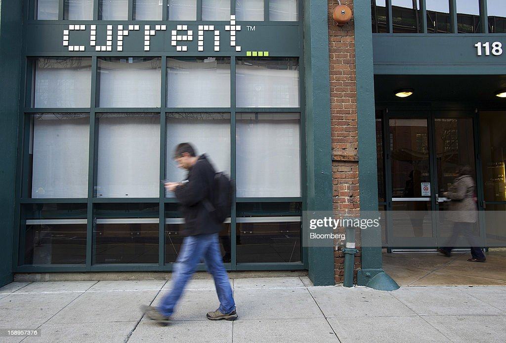 A man checks a mobile device as he walks past Current TV LLC headquarters in San Francisco, California, U.S., on Friday, Jan. 4, 2013. Al Jazeera will pay about $500 million for Current TV, including the stake held by former vice president Al Gore according to two people with knowledge of the deal. Photographer: David Paul Morris/Bloomberg via Getty Images