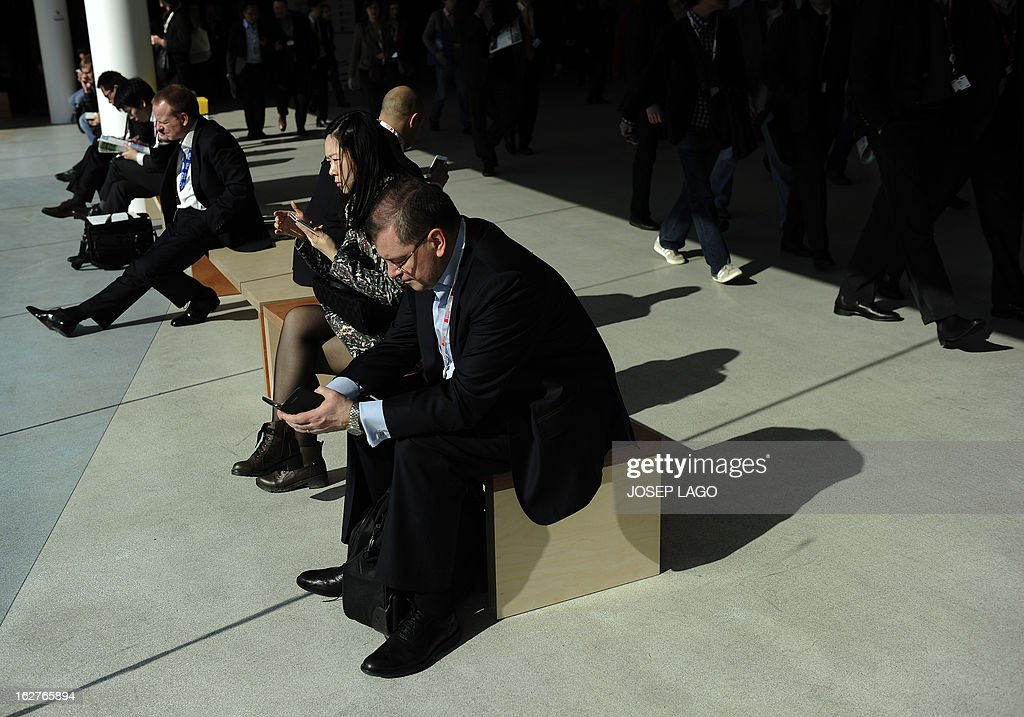 A man checks a mobile phone at the 2013 Mobile World Congress in Barcelona on February 26, 2013. The 2013 Mobile World Congress, the world's biggest mobile fair, is held from February 25 to 28 in Barcelona. AFP PHOTO / JOSEP LAGO