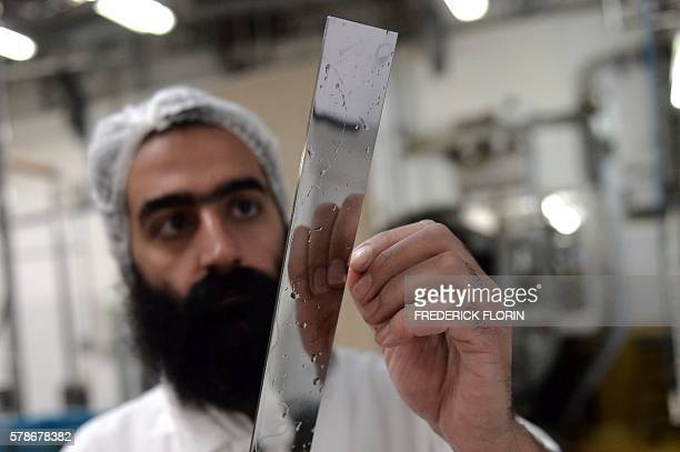 A man checks a 'shochet' knife before a Kosher ritual slaughter in Haguenau eastern France on July 21 2016 / AFP / FREDERICK FLORIN