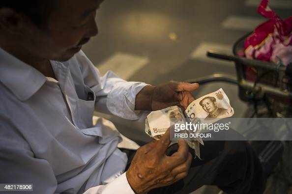 A man checks Chinese yuan bills in Beijing on July 28 2015 Chinese shares sank in the morning of July 28 a day after Shanghai's steepest slide in...