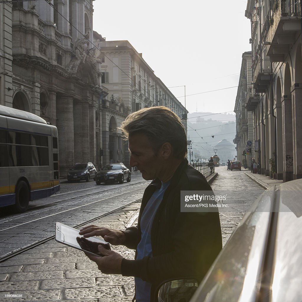 Man checks direction on digital tablet, on street : Stock Photo
