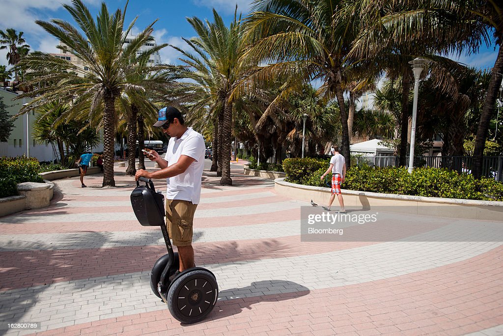 A man checks his cell phone while riding a Segway along the boardwalk in Miami Beach, Florida, U.S., on Wednesday, Feb. 20, 2013. U.S. exports in the travel and tourism sector reached $168.1 billion in 2012, up 10.1 percent from the year-ago level of $152.7 billion, according to data released Feb. 22 by the Commerce Department's International Trade Administration. Photographer: Ty Wright/Bloomberg via Getty Images