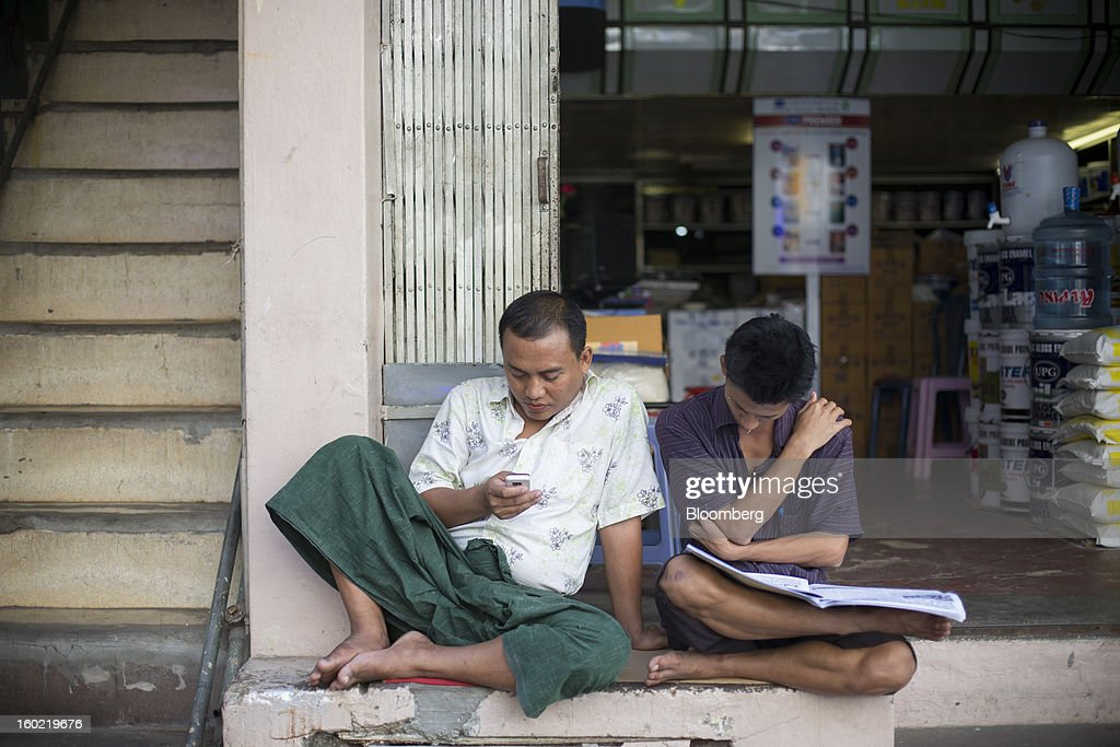 A man checks his mobile phone as another reads a newspaper in front of a store in Yangon, Myanmar, on Tuesday, Jan. 22, 2013. Myanmar cleared about $1 billion in overdue debt with the Asian Development Bank and World Bank using a bridge loan from Japan, opening the door for increased lending as the country seeks to overhaul its infrastructure. Photographer: Brent Lewin/Bloomberg via Getty Images