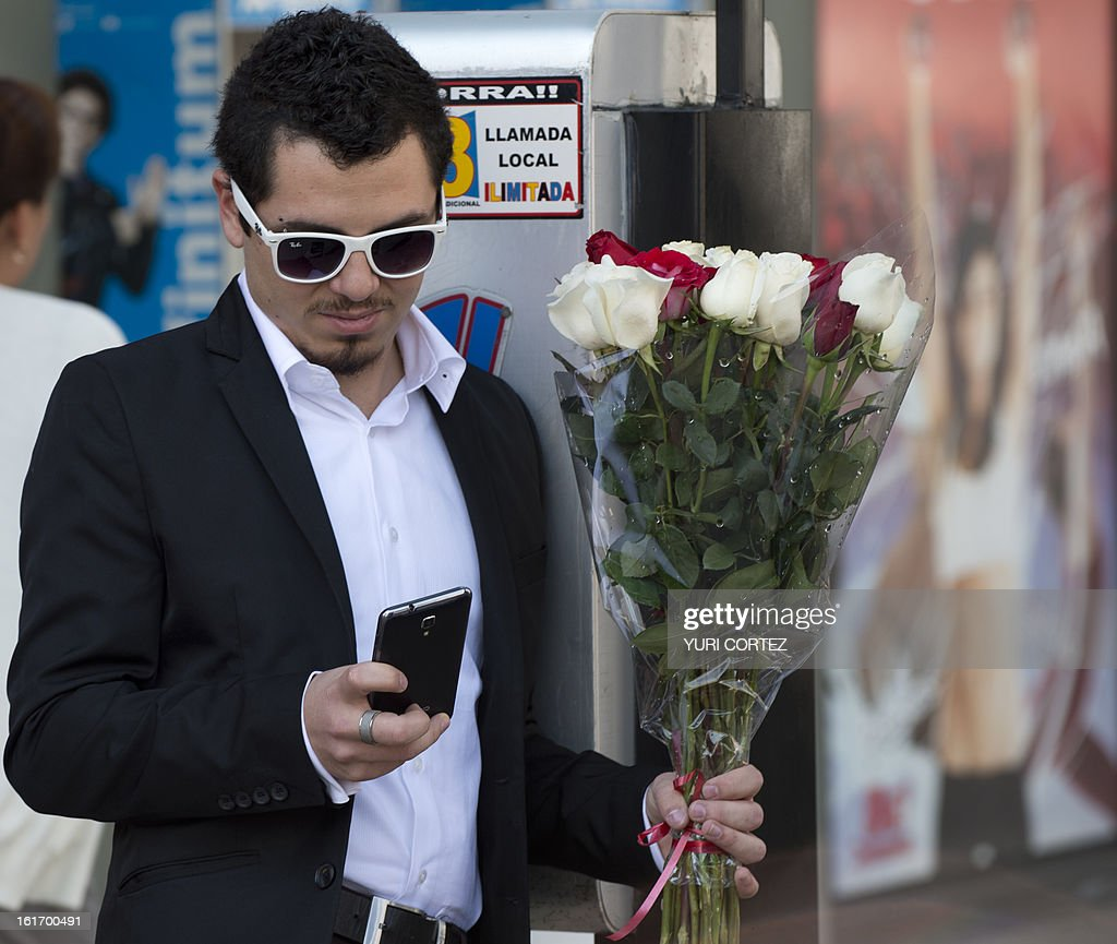 A man checks his mobile phone as he holds a bunch of flowers at the Republic Square in Mexico City on St Valentine's Day, on February 14, 2013. AFP PHOTO/Yuri CORTEZ