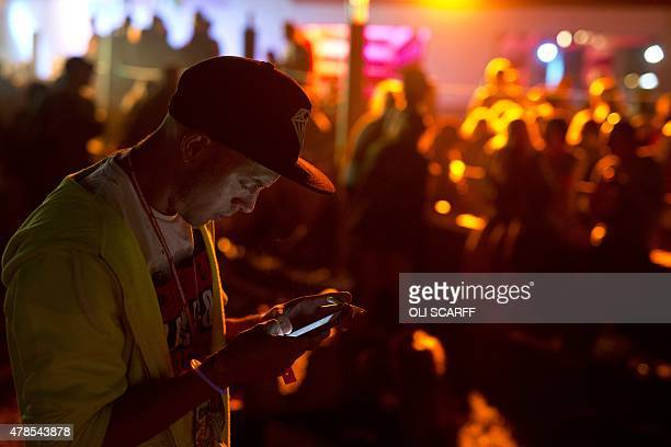 A man checks his mobile phone as revelers dance to music in the 'Silver Hayes' area at the Glastonbury Festival of Music and Performing Arts on...