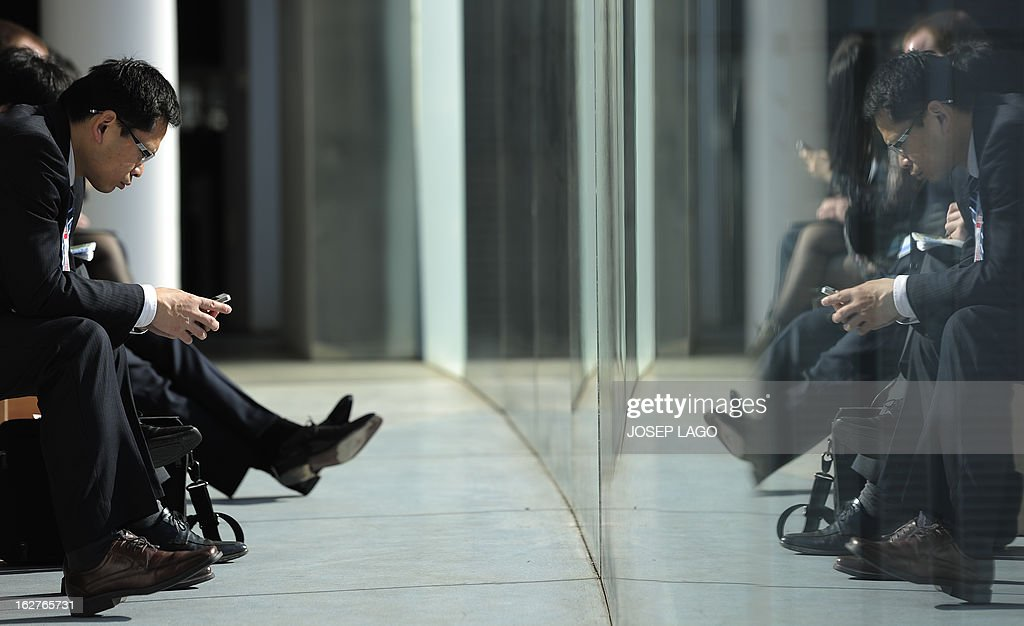 A man checks his mobile phone at the 2013 Mobile World Congress in Barcelona on February 26, 2013. The 2013 Mobile World Congress, the world's biggest mobile fair, is held from February 25 to 28 in Barcelona.