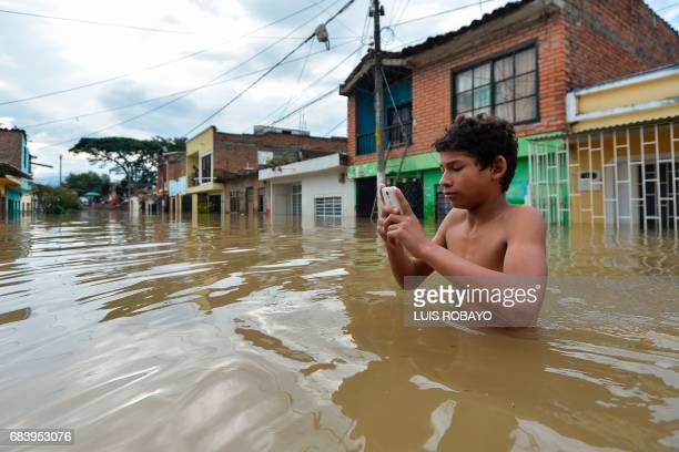 A man checks his mobile phone in a flooded street in Cali Colombia on May 16 after heavy rains caused the overflowing of the Cauca river Colombia...