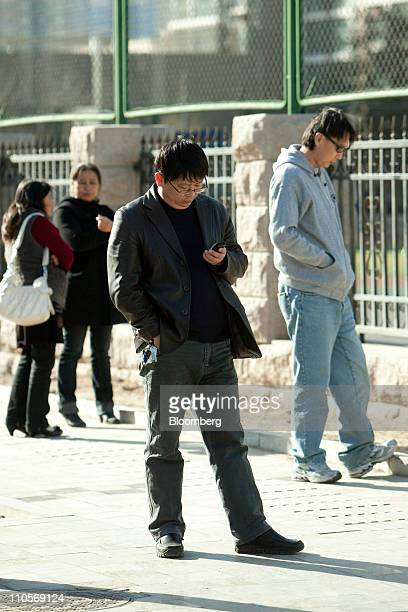 A man checks his mobile phone in Beijing China on Tuesday March 22 2011 China Telecom Corp the country's biggest fixedline carrier said it plans to...