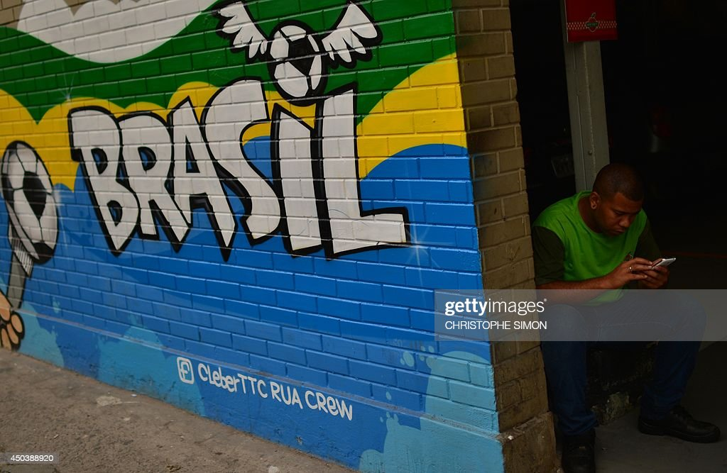 A man checks his mobile phone next to a decorated wall with Brazilian colors in a street on June 10, 2014, in Rio de Janeiro, Brazil.