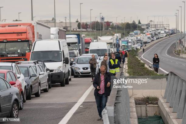 A man checks his mobile phone next to a traffic jam due to a blocked road during a regional strike on November 8 2017 in Riudellots de la Selva Spain...