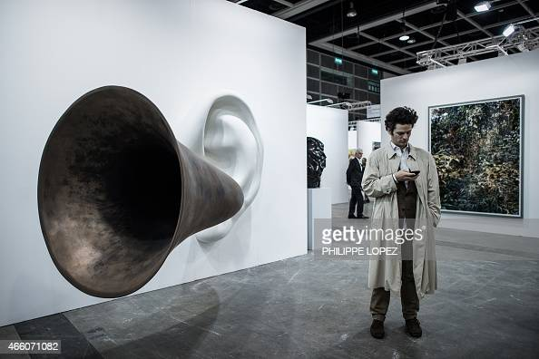 A man checks his mobile phone next to an artwork by US conceptual artist John Anthony Baldessari during the opening of the Art Basel art fair for a...