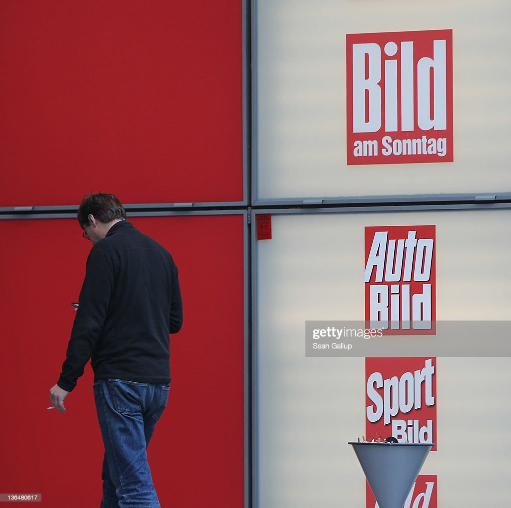 A man checks his mobile phone next to the editorial offices of Bild Zeitung, Germany's biggest tabloid newspaper, at Axel Springer Verlag publishing house corporate headquarters on January 6, 2011 in Berlin, Germany. Bild Zeitung Editor-in-Chief Kai Diekmann and German President Chistian Wulff are locked into a war of words over a message Wulff left on Diekmann's mobile phone in which he reportedly demanded that Bild not publish a compromising story about Wulff's personal financial conduct while governor of Lower Saxony. In a recent television interview Wulff claimed he only asked Diekmann to postpone publication of the story by a day.