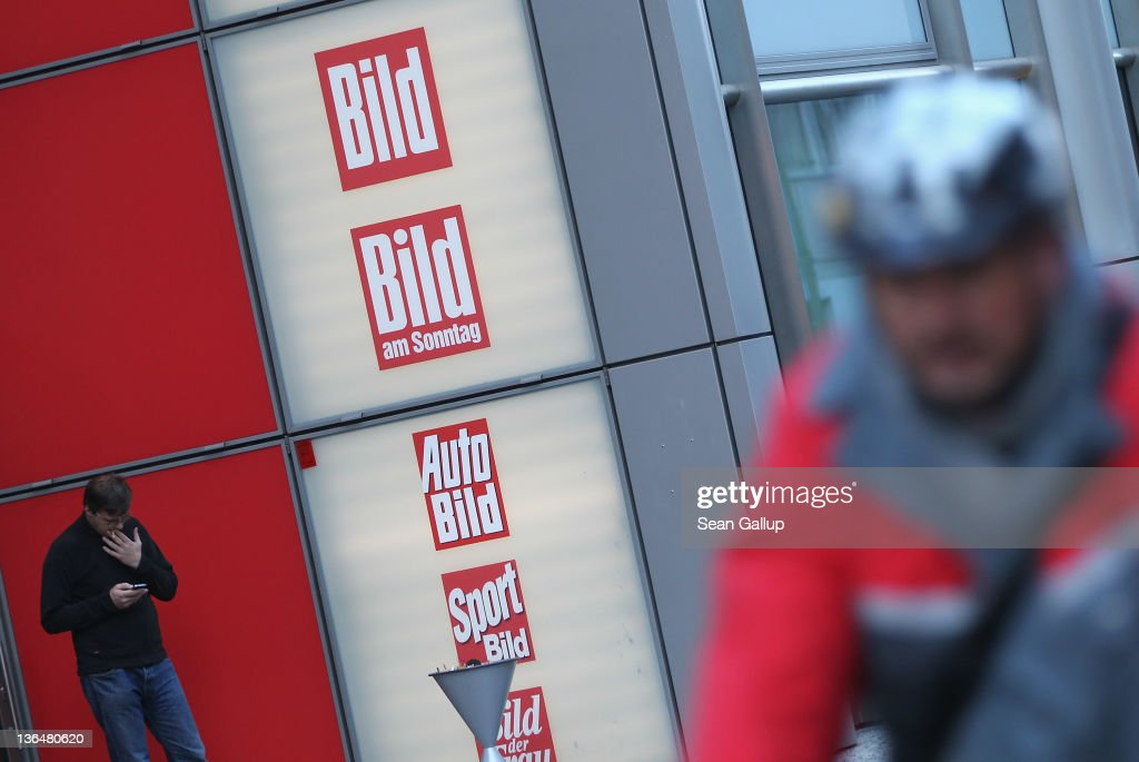 A man checks his mobile phone next to the editorial offices of Bild Zeitung, Germany's biggest tabloid newspaper, at Axel Springer Verlag publishing house corporate headquarters as another man on a bicycle rides past on January 6, 2011 in Berlin, Germany. Bild Zeitung Editor-in-Chief Kai Diekmann and German President Chistian Wulff are locked into a war of words over a message Wulff left on Diekmann's mobile phone in which he reportedly demanded that Bild not publish a compromising story about Wulff's personal financial conduct while governor of Lower Saxony. In a recent television interview Wulff claimed he only asked Diekmann to postpone publication of the story by a day.