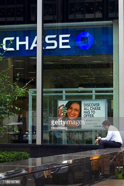 A man checks his mobile phone while sitting in front of a JPMorgan Chase Co bank branch in New York US in New York US on Friday July 8 2011...