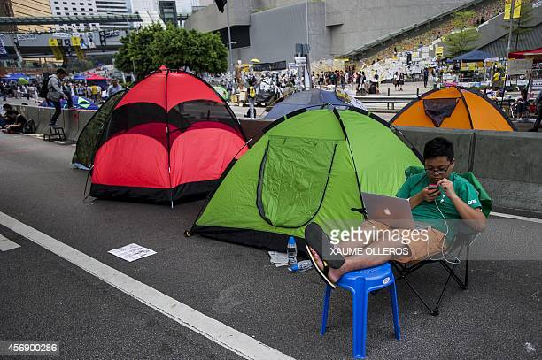 A man checks his phone at Admiralty district on October 9 2014 in Hong Kong Hong Kong has been plunged into the worst political crisis since its 1997...