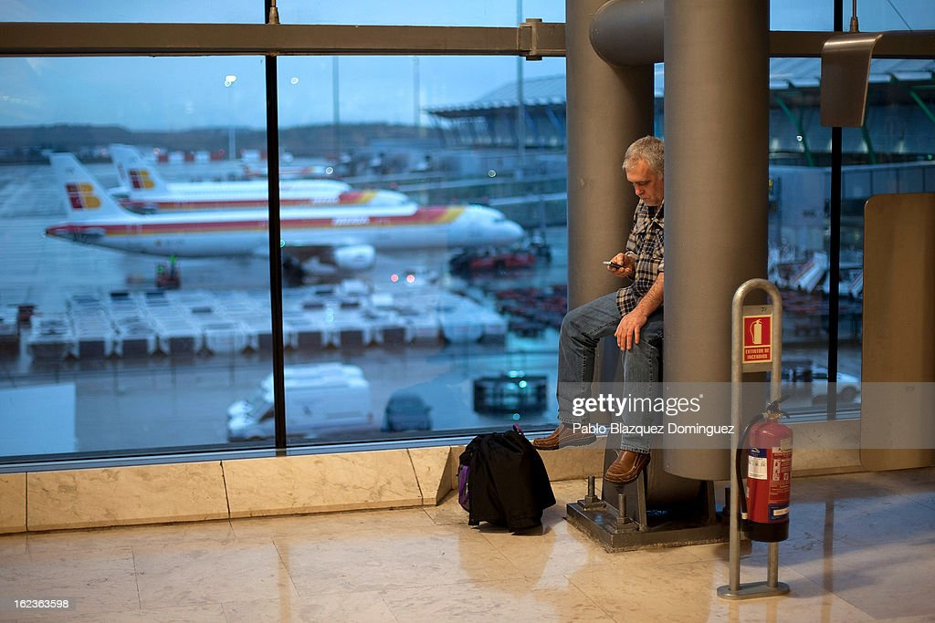 A man checks his phone at Barajas Airport while a fleet of Iberia planes are seen parked on February 22, 2013 in Madrid, Spain. Today is the last of a five day strike held by Iberia cabin crew, maintenance workers and ground staff in response to the planned loss of 3,800 jobs. The strike has resulted in the airline having to cancel 400 flights this week with unions planning more five day strikes in the following weeks.
