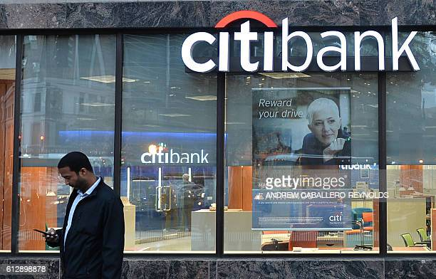 A man checks his phone near a Citibank branch on October 5 2016 in Washington DC Wall Street stocks gained led by petroleum companies due to higher...