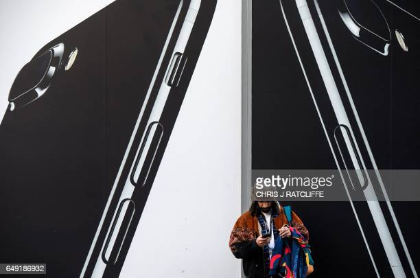 A man checks his phone next to billboards advertising the an Apple iPhone 7 smartphone as he stands on Oxford Street in London on March 7 2017...