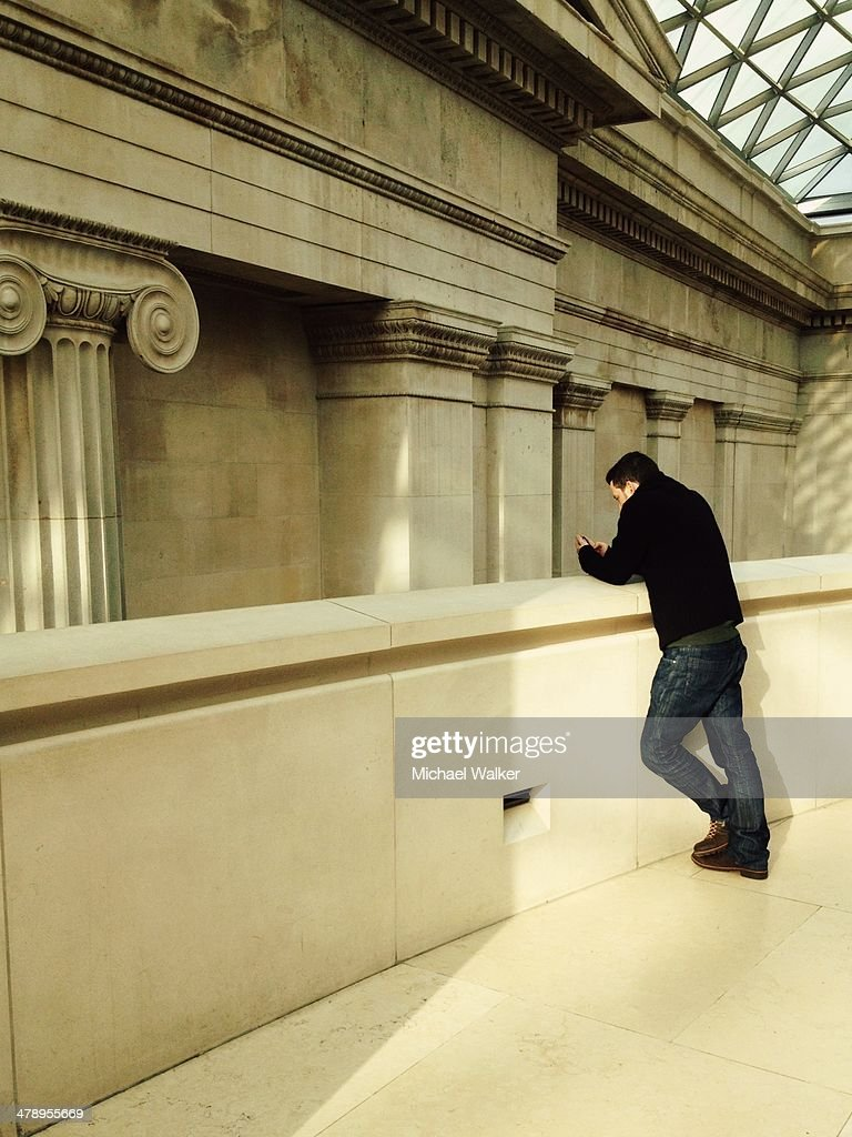 A man checks his social media on his smartphone at the British Museum, London.