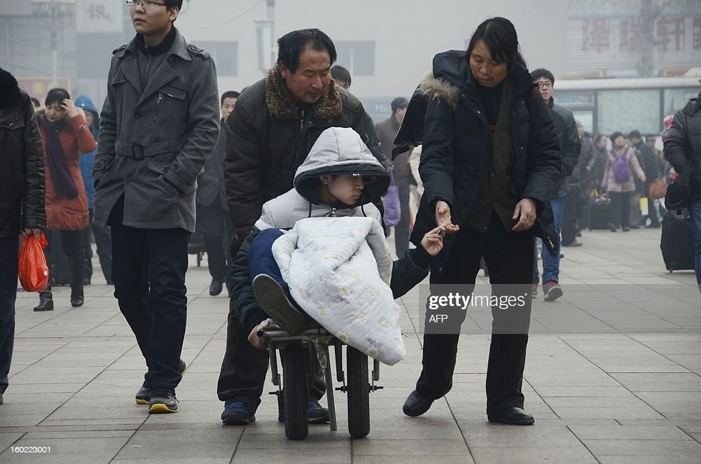 A man (C) checks his train ticket as he sits on a wheelbarrow contraption, pushed by his family before boarding a train at the Beijing railway station on January 28, 2013. The world's largest annual migration began on January 26 in China with tens of thousands in the capital boarding trains to journey home for next month's Lunar New Year celebrations.