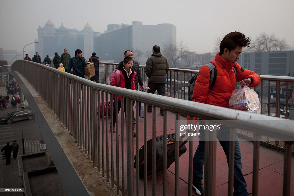 A man checks his watch as he walks across a bridge towards Beijing Railway Station in Beijing on January 27, 2013. The world's largest annual migration began in China with tens of thousands in the capital boarding trains to journey home for next month's Lunar New Year celebrations. AFP PHOTO / Ed Jones