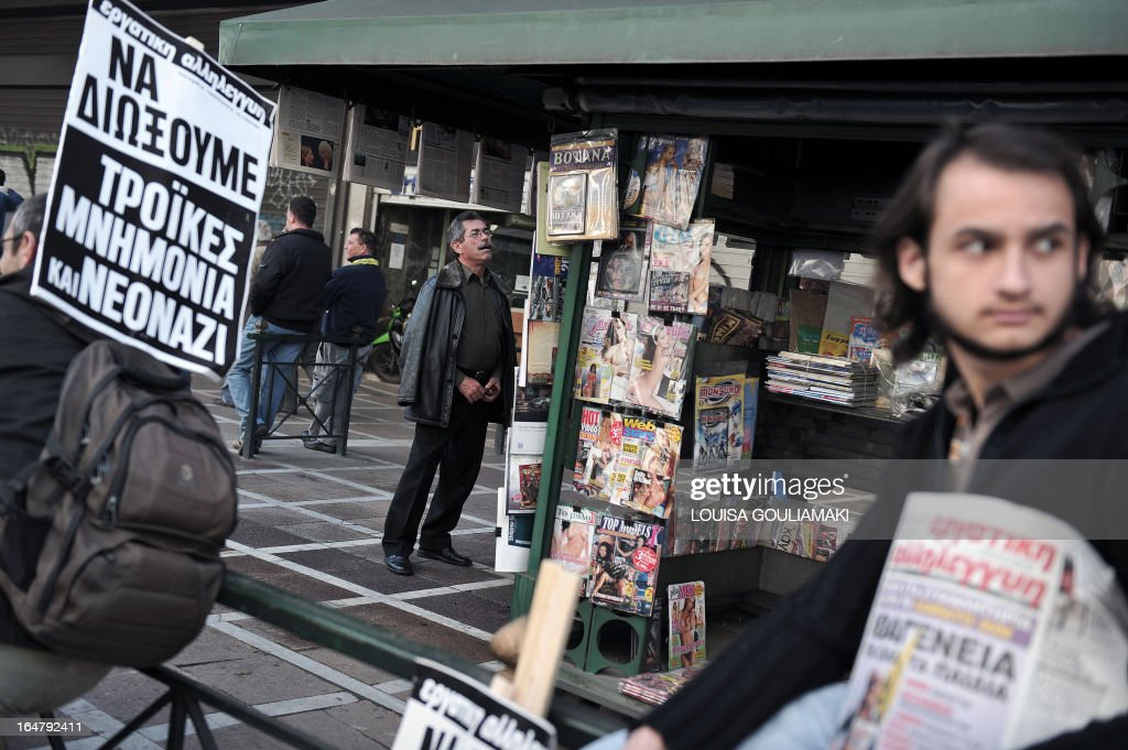 A man checks newspapers at a press booth while metal workers hold placards reading ''workers solidarity-to dismiss troika, memorandum, neonazis'' during a rally against government's austerity measures and high unemployment in their sector in central Athens on March 28, 2013. AFP PHOTO / LOUISA GOULIAMAKI