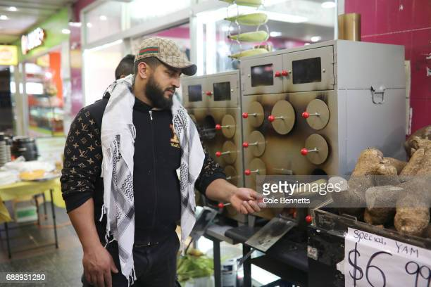 A man checks on a corn cob BBQ in the southwestern suburb of Lakemba during a street festival on May 27 2017 in Sydney Australia Muslims around the...