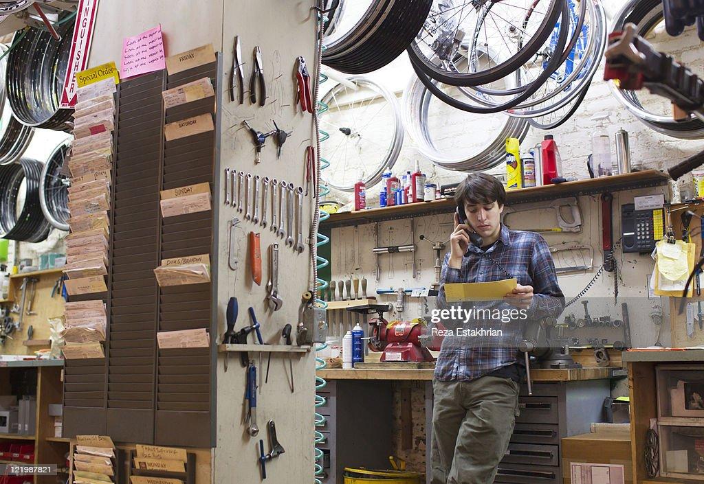 Man checks order in bike service shop : Stock Photo