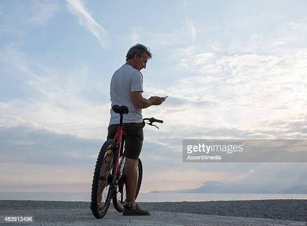 Man checks text from bicycle saddle, at beach