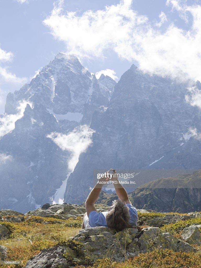 Man checks text message, below mountain peak : Stock Photo