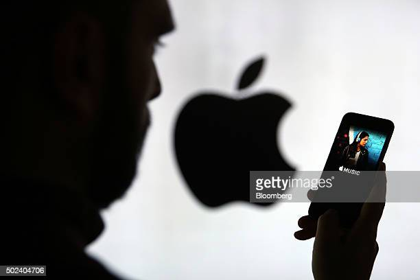 A man checks the Apple Music streaming site using his Apple Inc iPhone 6s as he stands framed against a wall bearing the Apple logo in this arranged...
