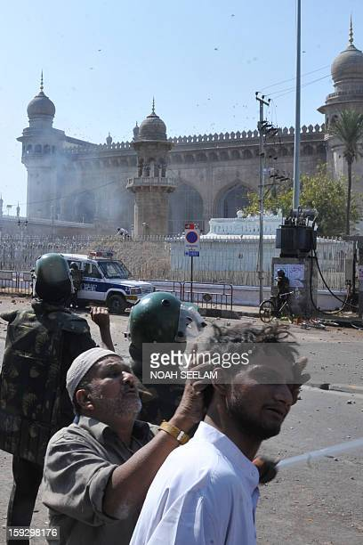 A man checks the head of an injured demonstrator as riot police clash with supporters of the MajliseIttehadul Muslimeen outside the historic Mecca...