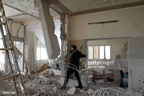 A man checks the inside of a house in the southern city of Sweida on January 23 2013 The two provinces are diametrically opposed in the current...