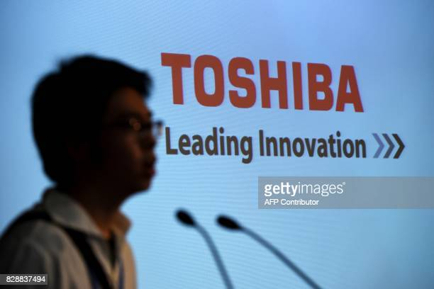 A man checks the microphones next to a logo of Toshiba prior to a press conference at the company's headquarters in Tokyo on August 10 2017 Toshiba...