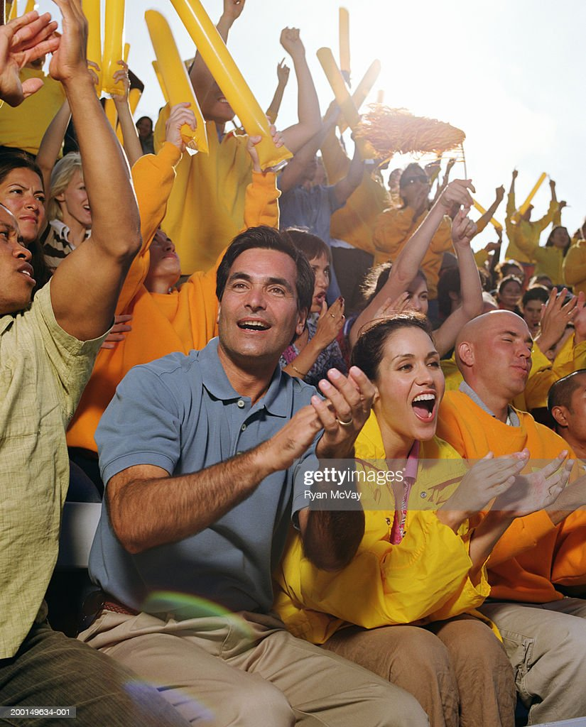 Man cheering with crowd in stadium : Stock Photo