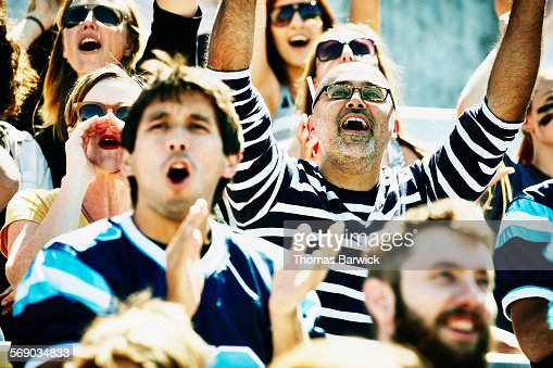Man cheering with friends in stadium during game