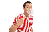 Joyful man chewing a gum and blowing a bubble isolated on white background
